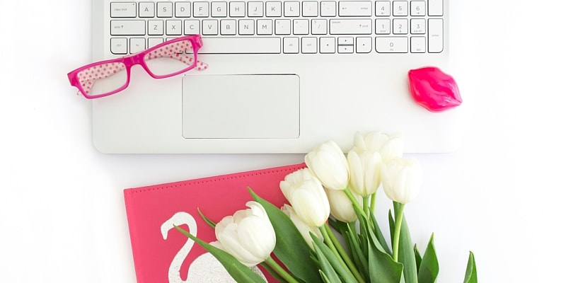 Laptop For Blogging And Using WordPress With Bright Pink Notebook, Glasses And White Tulips