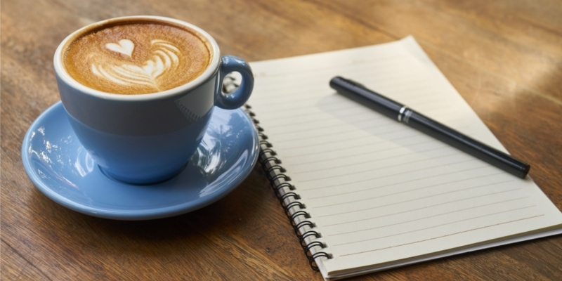 Bloggers Blue Mug Of Coffee With Notebook And Pen Ready To Take Notes On WordPress Permalinks
