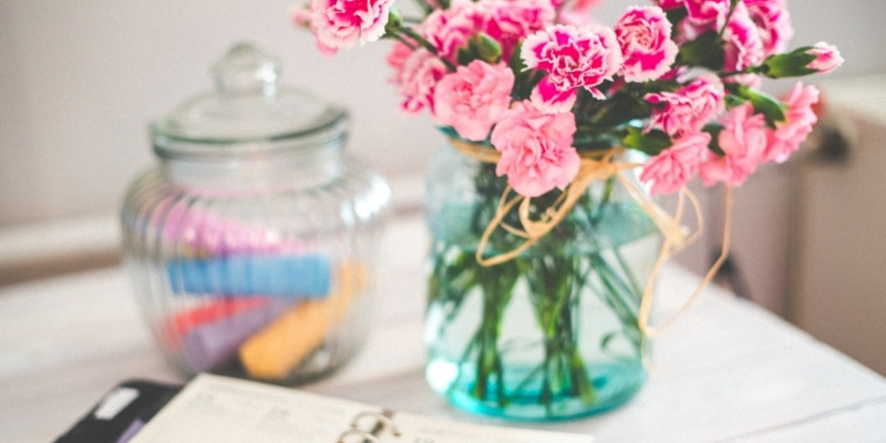 Bloggers Desk With Journal Planner Jar Of Chalk And Vase Of Pink Flowers