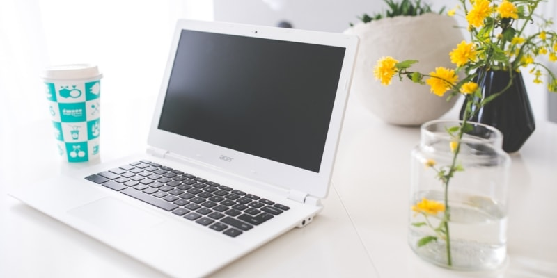 Bloggers Acer Chromebook On A White Desk With A Blue Coffee Cup