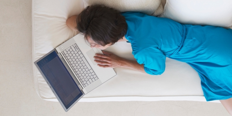 Female Blogger On Sofa In Blue Dress Learning How To Write Blog Posts Faster
